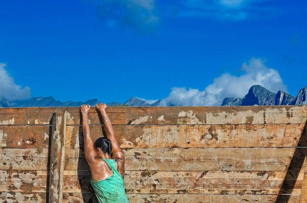 Franchir un obstacle - femme suspendue à un mur