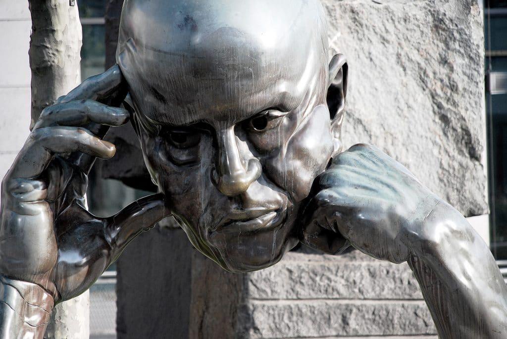 Sculpture métallique d'une tête d'homme en train de penser